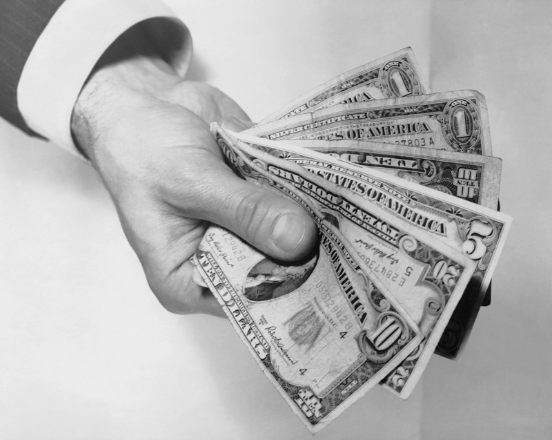 black and white photo of hand holding out money