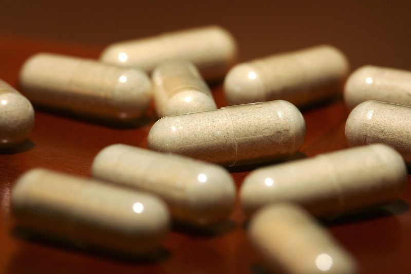 White diet pills laying on a wooden surface