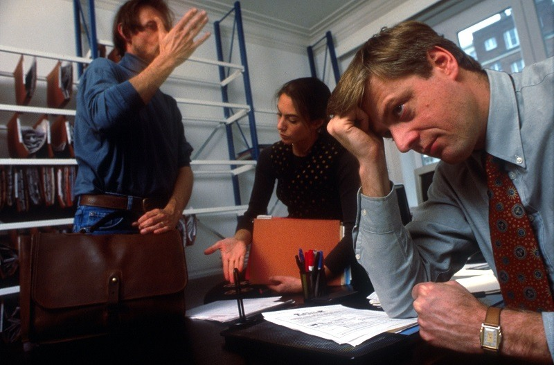 A man trying to work but surrounded by office commotion