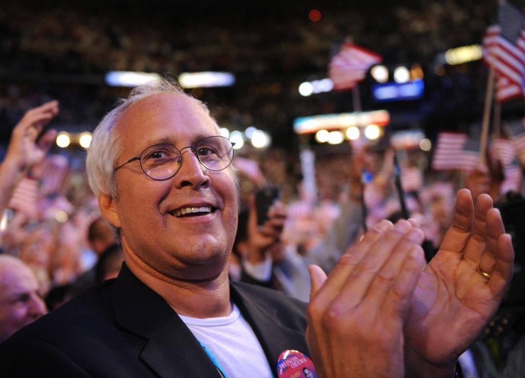Chevy Chase stands and claps at a rally