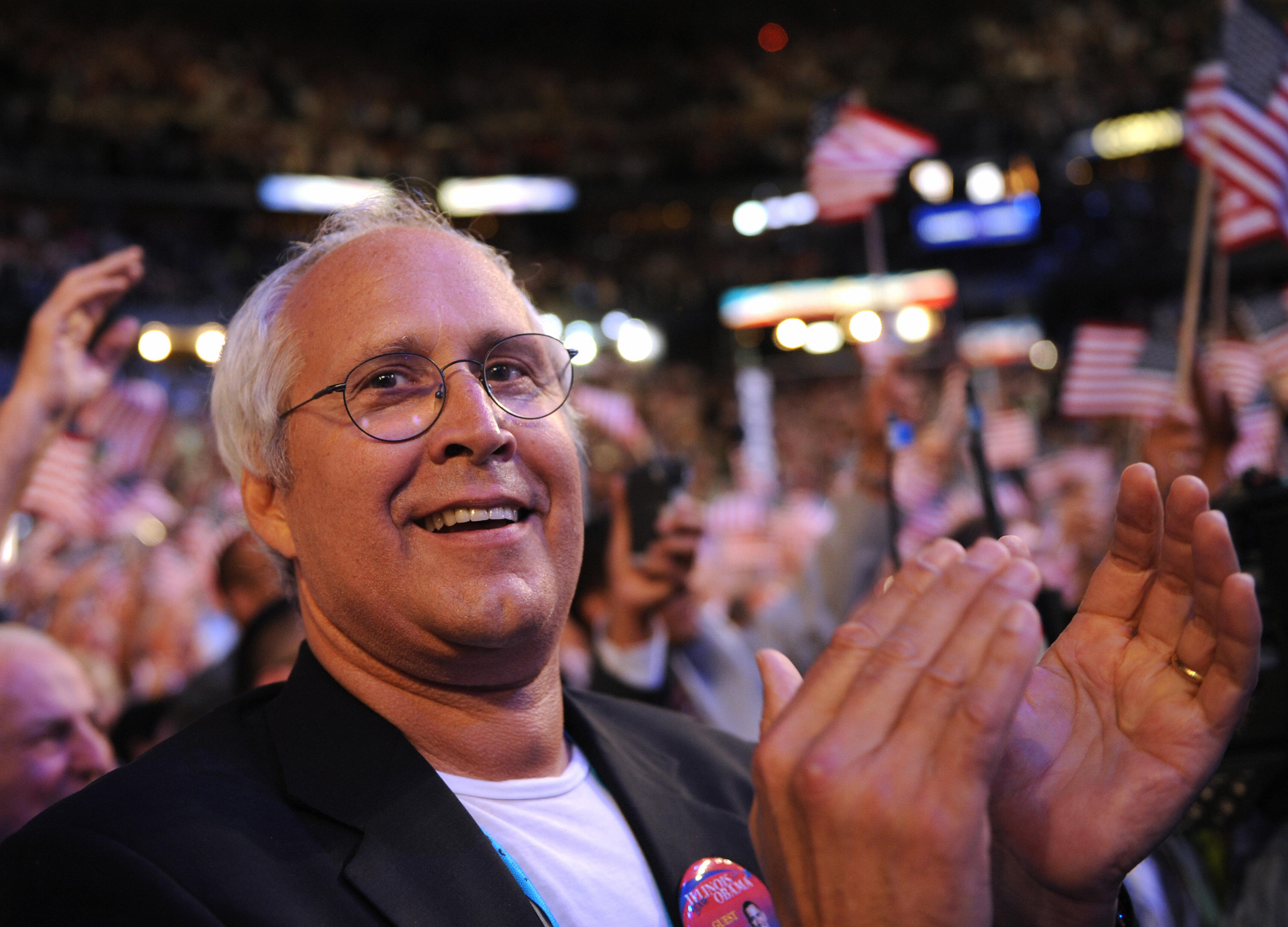 Chevy Chase clapping at a political rally