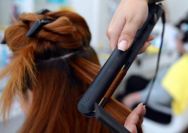 Hairdresser uses a hair straightener as she dresses a client's hair