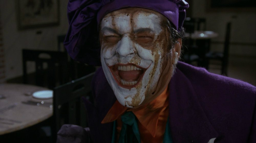 Jack Nicholson as the Joker wearing a purple suit and smiling gleefully while smeared makeup drips down his white face in 'Batman'