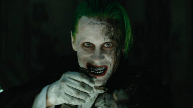 Joker smiles while holding his hand to his face.