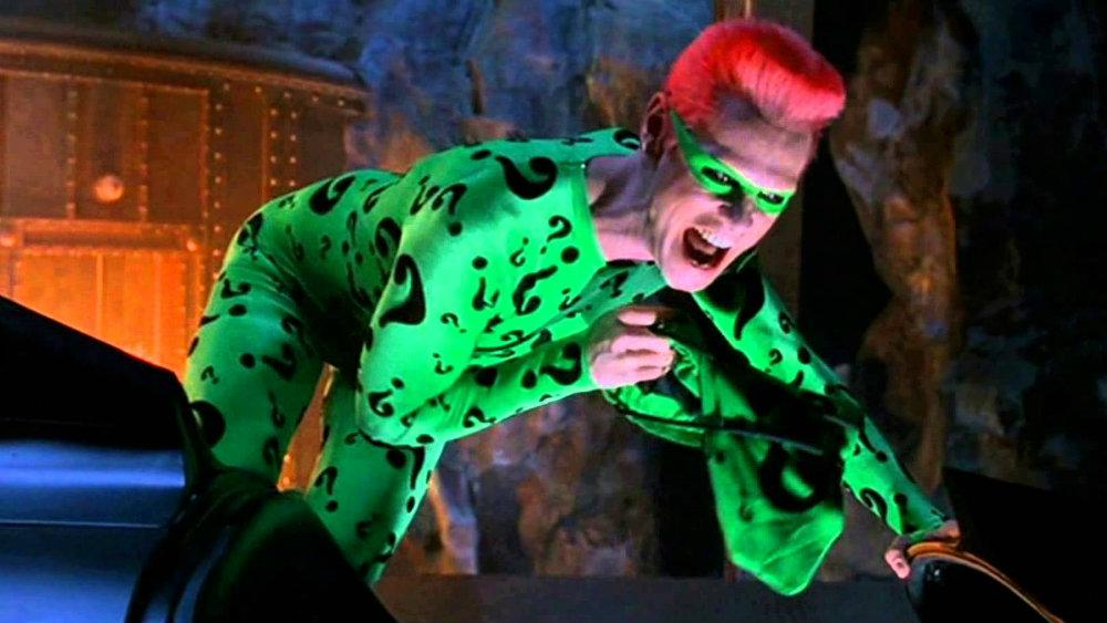 Jim Carrey as the Riddler wearing a green suit covered in question marks while smiling dementedly in 'Batman Forever'