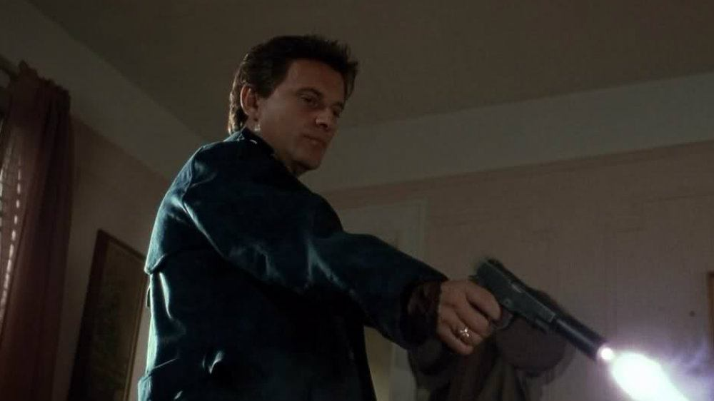 Joe Pesci as Tommy shooting a gun downward in Goodfellas