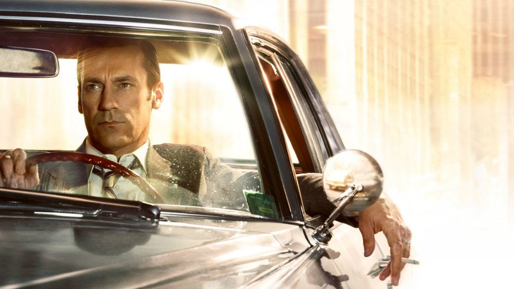 Jon Hamm as Don Draper in a suit driving a car in Mad Men