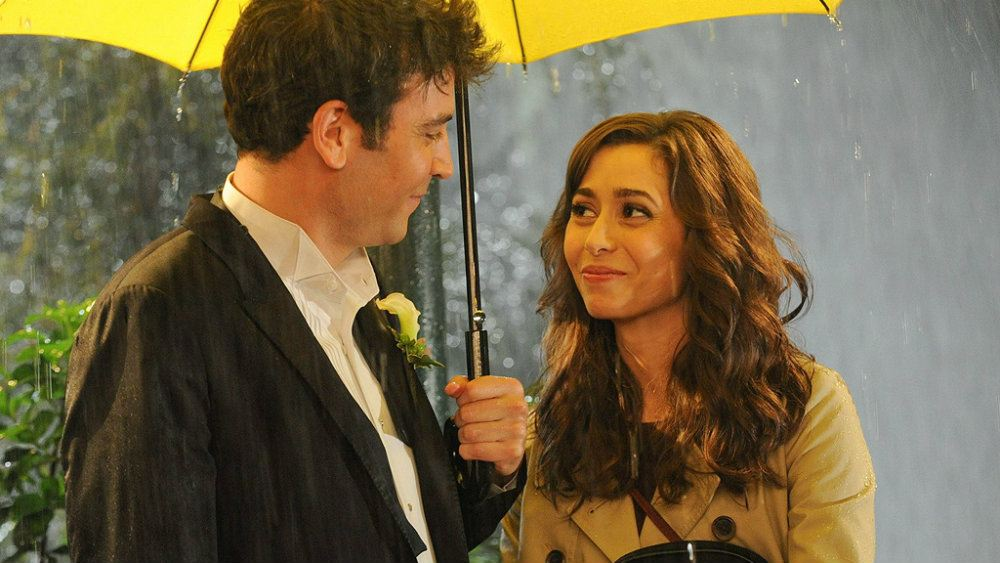 Josh Radner and Cristin Milioti standing under a yellow umbrella in the rain in How I Met Your Mother