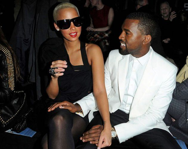 Kanye West and Amber Rose sit together at a fashion show.
