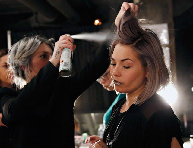 Lead hair stylist Stephanie Hayes uses Batiste Dry Shampoo backstage at the Charlotte Ronson Fall 2014 Presentation during Mercedes-Benz Fashion Week