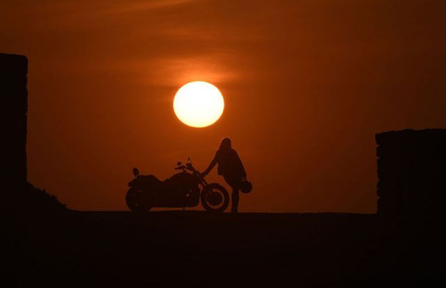 TOPSHOT - Mai Zniber, a Moroccan therapist poses at sunset next to her Harley Davidson motorbike on December 24, 2015 in the Moroccan capital Rabat. Mai has been riding a motorbike for four years and for her biking gives her a sense of freedom, self-confidence and pushes her limits with the bikes power and potential. / AFP / FADEL SENNA