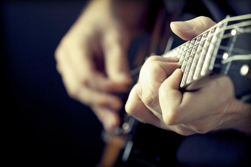 hands close of man playing guitar