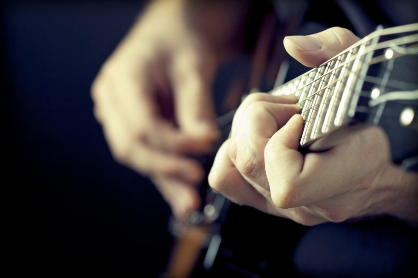 hands close of man playing guitar