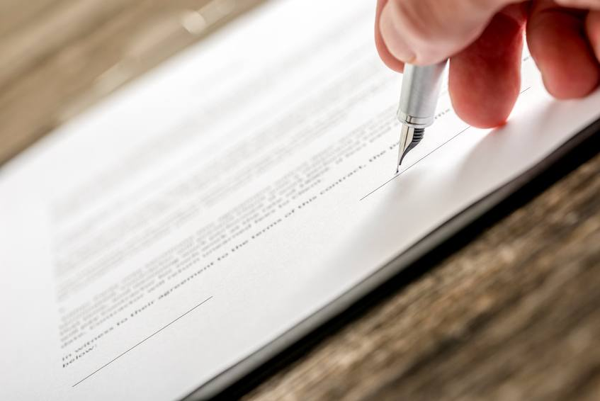 Man signing business document