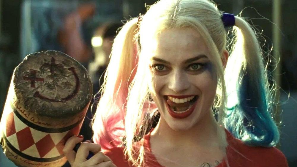 Margot Robbie in Harley Quinn makeup and smiling while holding a giant mallet in Suicide Squad