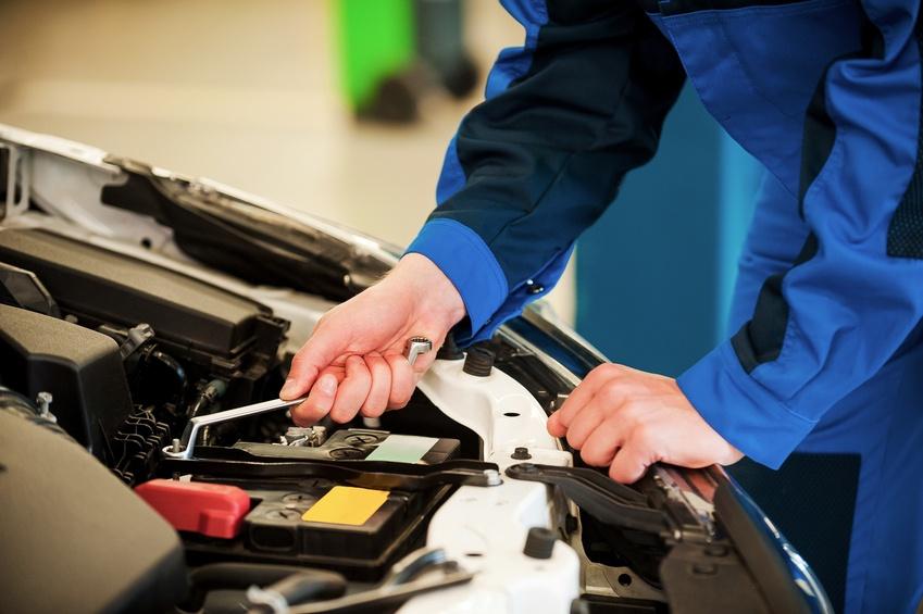 man in blue uniform repairing car