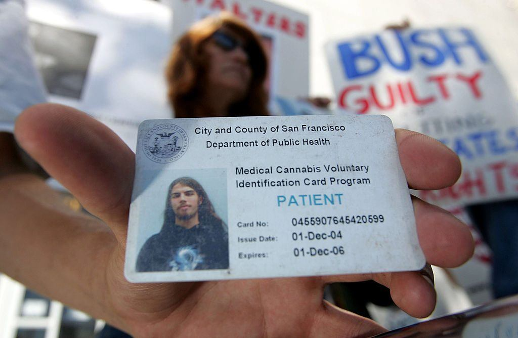 Lucas Thayer holds his medical marijuana ID card during a demonstration in front of the San Francisco Hall of Justice July 12, 2005 in San Francisco, California. | Justin Sullivan/Getty Images