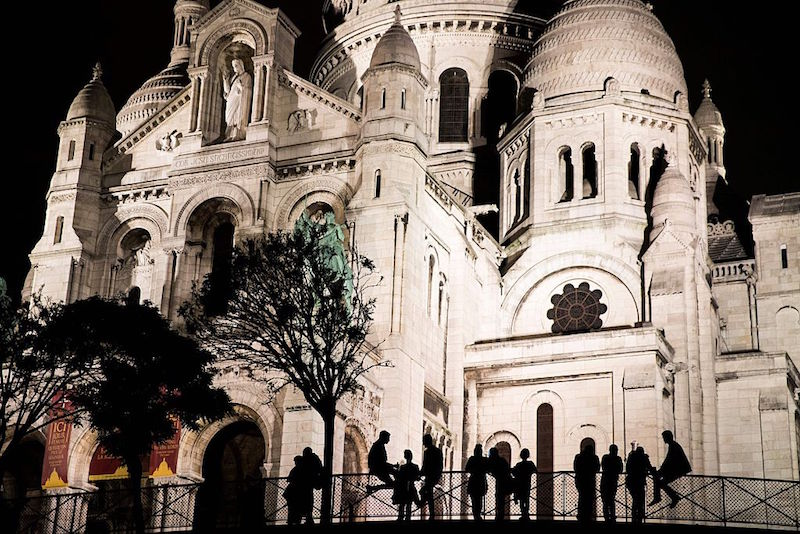 People are seen silhouetted sitting on a fence in front of the landmark church Sacre Couer in Paris late on June 21, 2016
