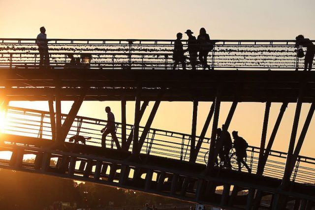 People walk on a bridge above the river Seine in Paris at sunset on September 10, 2015. AFP PHOTO / LUDOVIC MARIN