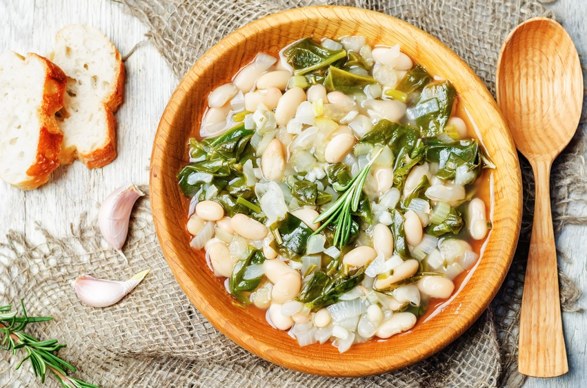 white bean spinach soup in a wooden plate with wooden spoon