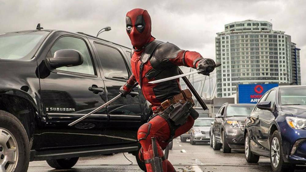 Ryan Reynolds in Deadpool standing with his weapons in a traffic jam