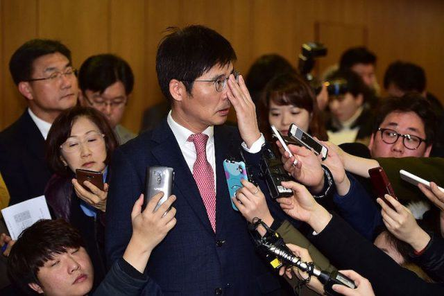 """Samsung Electronics' chief negotiator Baek Soo-Hyun (C) adjusts his glasses as he is surrounded by reporters after an agreement aiming to improve health and safety conditions at all Samsung's plants, in Seoul on January 12, 2016. Samsung Electronics said it had signed """"a final settlement"""" over workers who contracted cancer in its semiconductor plants, but a victims' advocacy group said key issues remained unresolved. AFP PHOTO / JUNG YEON-JE / AFP / JUNG YEON-JE"""