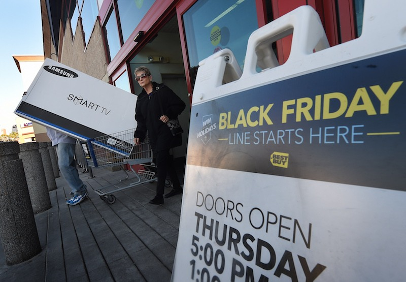"""Shoppers leave a Best Buy store with a television during a Black Friday sale in Los Angeles, California on November 27, 2015. The US holiday shopping season kicks off with """"Black Friday"""" -- the day after the Thanksgiving holiday -- with a frenzy expected at stores around the country as retailers slash prices. AFP PHOTO/ MARK RALSTON / AFP / MARK RALSTON"""