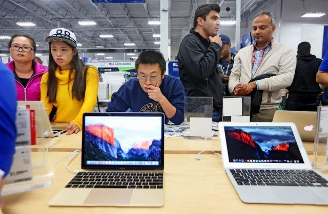 Shoppers look over computer items at a Best Buy
