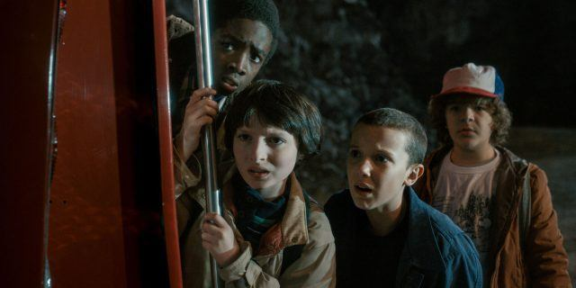 Lucas, Mike, Eleven and Dustin look worried in a scene from Season 1 of 'Stranger Things'