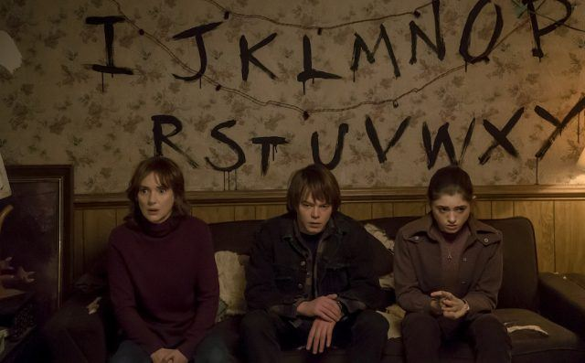 Joyce (Winona Ryder), Jonathan (Charlie Heaton) and Nancy (Natalia Dyer) sit on the couch in a scene from 'Stranger Things'