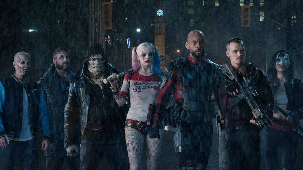 The Suicide Squad villains walk in a formation in the rain