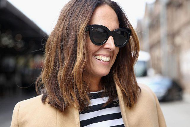 Woman in coat and sunglasses with horizontal stripe shirt on