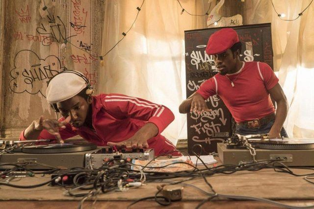 Two men in red and white outfits spinning and playing music surrounded by recording equipment.