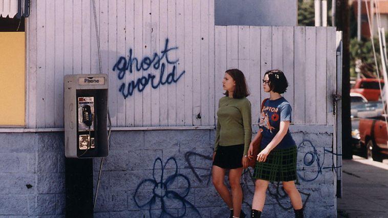 "Scarlett Johansson and Thora Birch walk next to a white fence that reads ""Ghost World"""