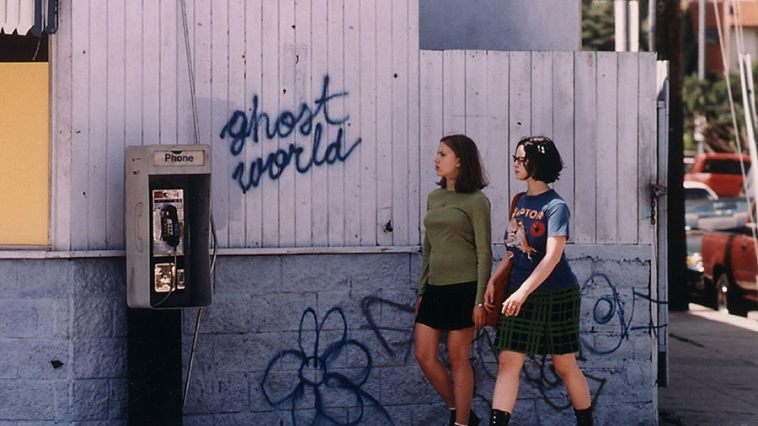 "Scarlett Johansson and Thora Birch walk next to a white fence that reads ""Ghost World"""