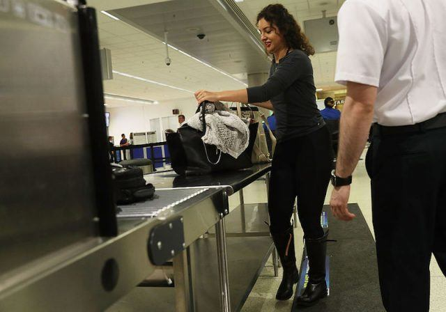 MIAMI, FL - JUNE 02: Travelers go through the TSA PreCheck security point at Miami International Airport on June 2, 2016 in Miami, Florida. As the busy summer travel season heats up the Transportation Security Administration is encouraging people to sign up for the TSA PreCheck program to save time going through the airports security lines. Those enrolled in the program can leave their shoes, light outerwear and belt on during the terminal screening process as well as keeping their laptop in the carry-on suitcase without having to remove them at the checkpoint.