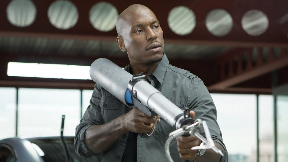 Tyrese Gibson holds a giant silver gun in Fast & Furious 6