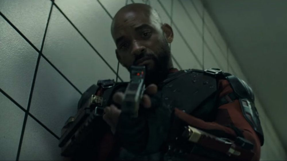 Will Smith is pointing a gun downward in Suicide Squad.