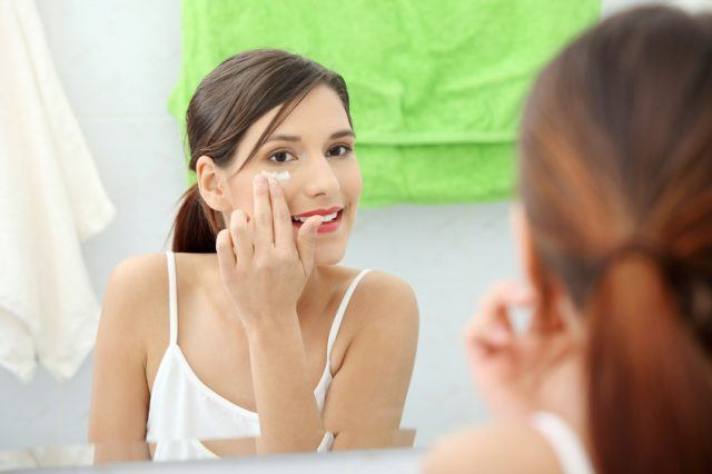 Woman applying moisturizer cream in front of mirror