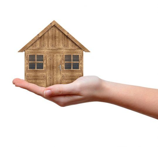 Small wooden house model in hand
