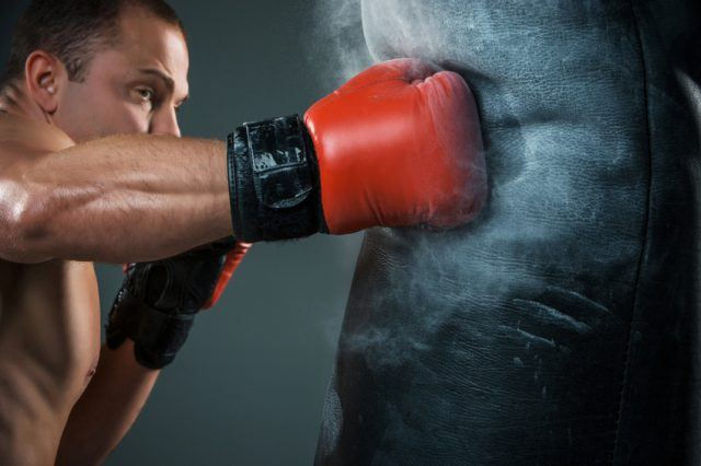 Young boxer wearing red gloves working on punching bag.