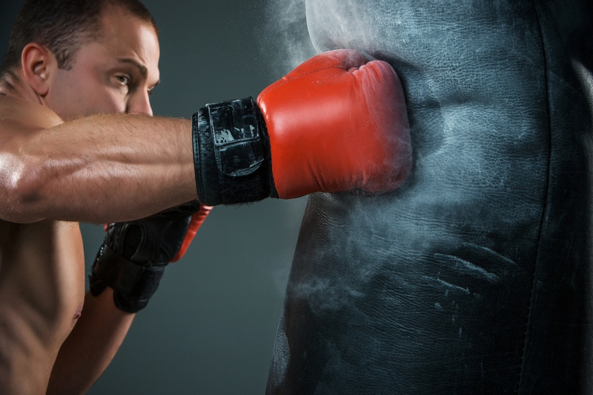 Young boxer wearing red gloves working on punching bag