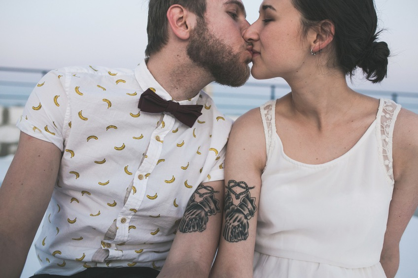 Young couple with matching tattoos kissing