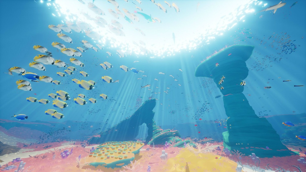 Fish swim in a colorful underwater environment.