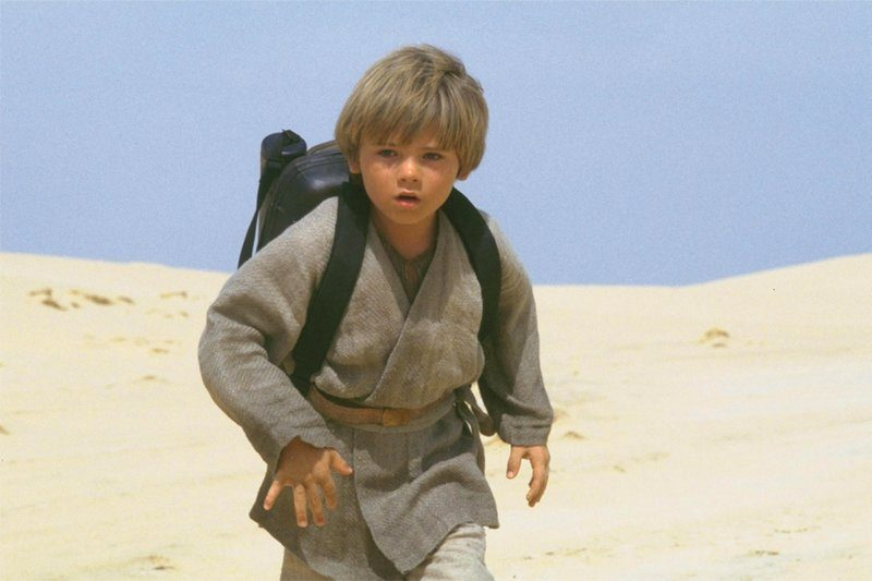 A young Anakin wearing a backpack, running through the desert