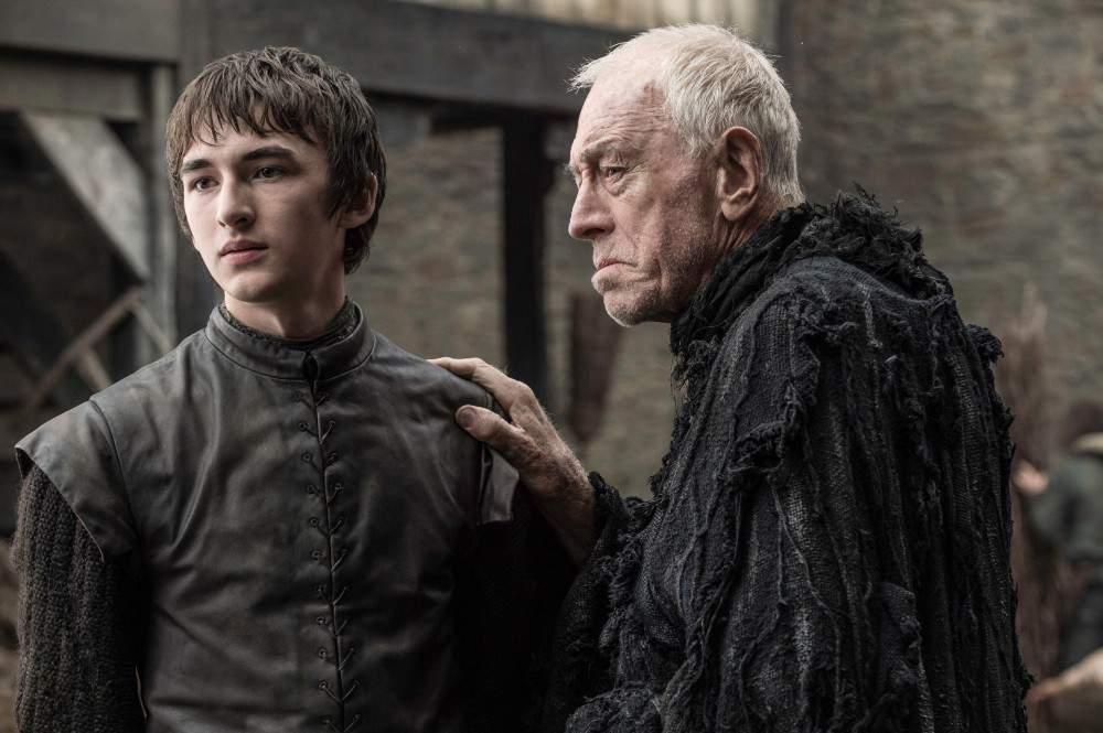 The Three Eyed Raven puts his hand on Bran's shoulder, as they both look off to the left of the frame