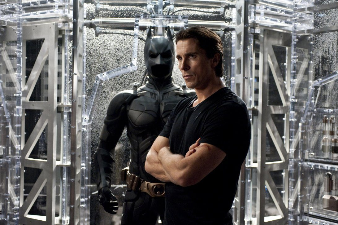 Christian Bale as Bruce Wayne standing in front of a Batman costume.