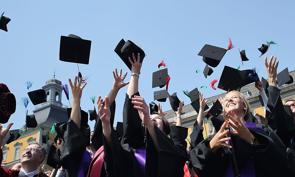 Students throw their hats in the air at their college graduation