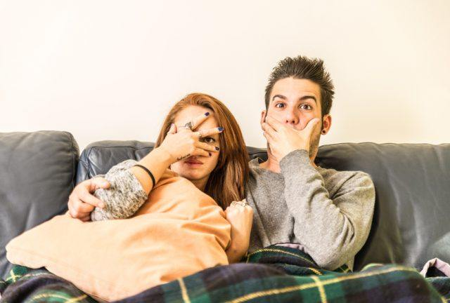 Couple watching horror movie on television on the couch