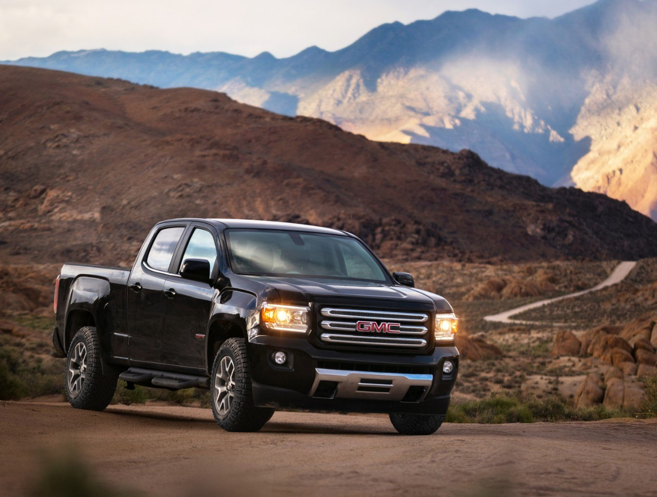 A black GMC Canyon parked on a scenic mountain range